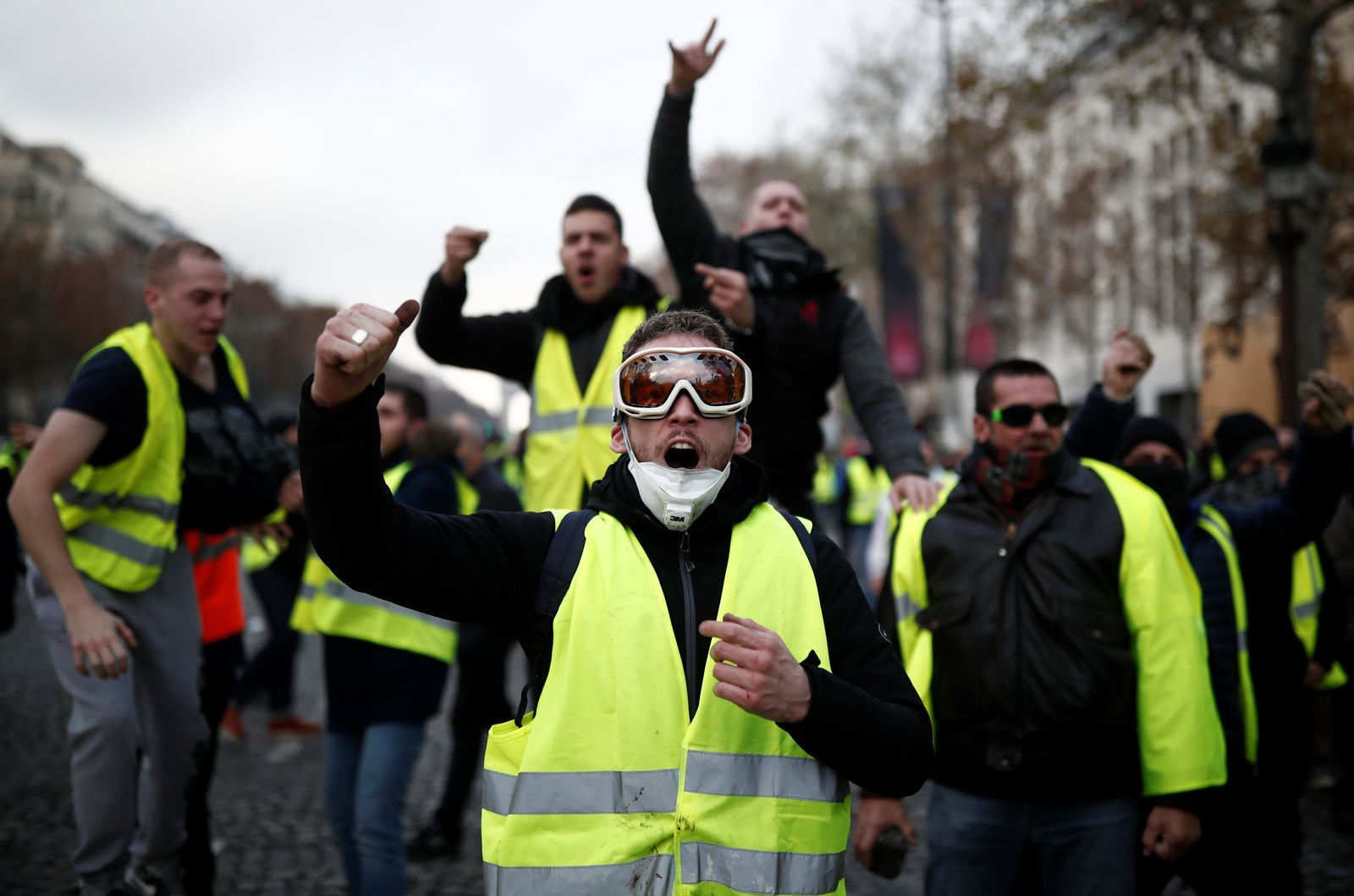 Protesters wearing yellow vest, a symbol of a French drivers' protest against higher fuel prices, shout out slogans on the Champs-Elysee in Paris