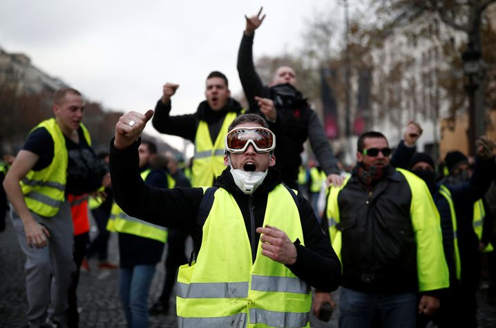 Protesters wearing yellow vest, a symbol of a French drivers' protest against higher fuel prices, shout out slogans on the Champs-Elysee in Paris, France, November 24, 2018. REUTERS/Benoit Tessier - RC19043111F0
