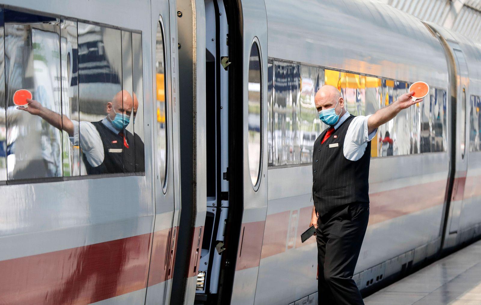 Deutsche Bahn Coronavirus Berlin, DEU, 27.05.2020 - Ein Zugbegleiter mit Gesichtsmaske gibt dem Lokfuehrer das Abfahrtze