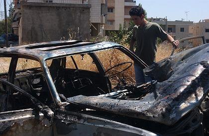 Ein Libanese betrachtet das Wrack eines Autos, das bei einem israelischen Luftangriff zerstört wurde.