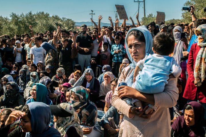 Im Flüchtlingscamp Moria hält eine Frau ein Baby auf dem Arm, während Dutzende Menschen wegen der schlechten Lebensbedingungen in dem Camp demonstrieren (Archivbild)