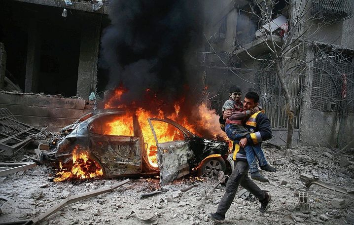 A Syria Civil Defense member carries a wounded child in the besieged town of Hamoria, Eastern Ghouta, in Syria in 2018.