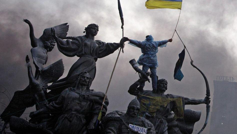 Demonstrant auf einem Denkmal während der Kämpfe am Maidan in Kiew im Februar