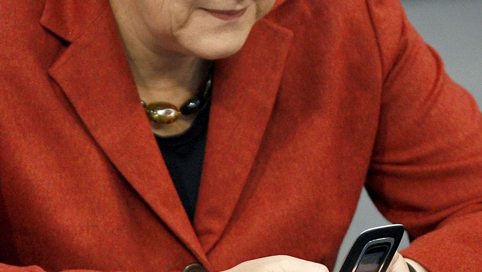 """Bundeskanzlerin Angela Merkel (CDU) mit Handy: """"Mach ich bestimmt."""""""
