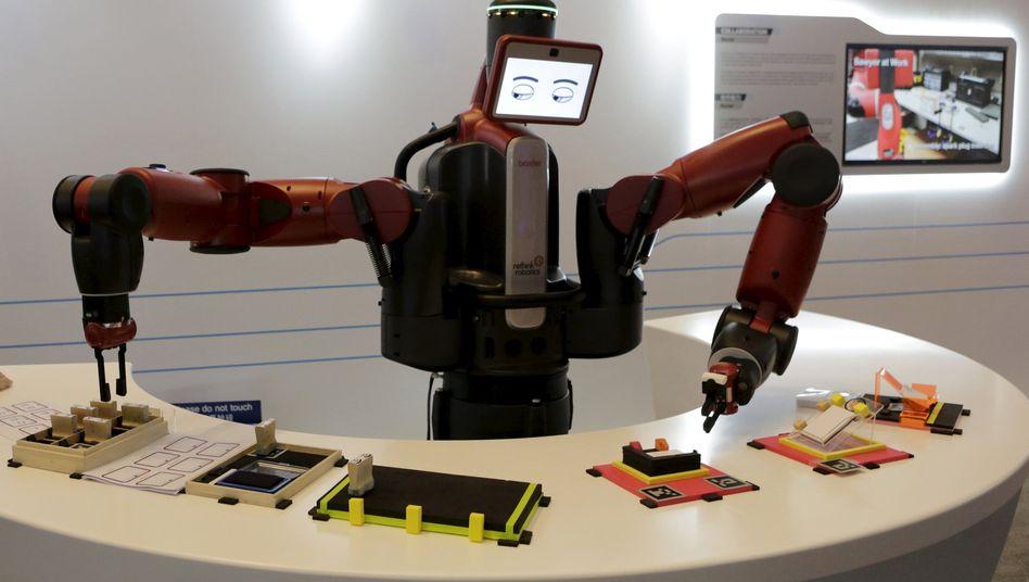 Ein Roboter greift eine Visitenkarte: Digitalisierung bedroht fünf Millionen Jobs
