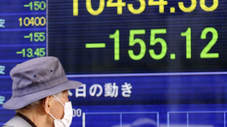 Massives Minus: Ein Mann in Tokio betrachtet die Reaktion der Aktienmärkte