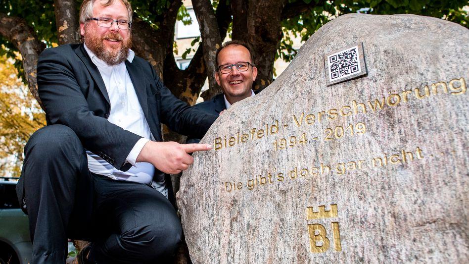 """Martin Knabenreich (r), Geschäftsführer Bielefeld Marketing und Achim Held (l) aus Kiel, """"Schöpfer"""" der """"Bielefeld-Verschwörung, präsentieren das Denkmal für die Bielefeld-Verschwörung."""