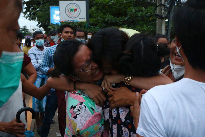 Zwei Frauen umarmen einen Mann nach dessen Entlassung aus dem Gefängnis
