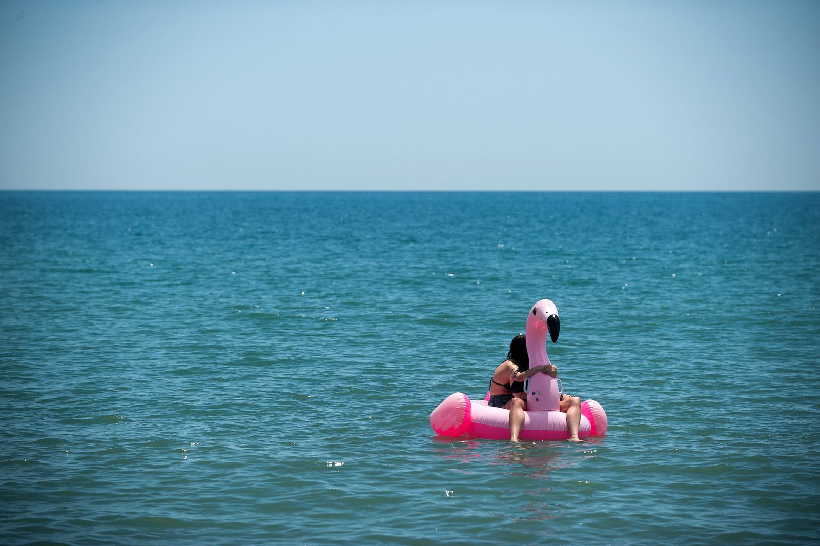 June 1, 2020, Malaga, Spain: Two people are seen on a float in a form of a swan at Misericordia beach as they enjoy the