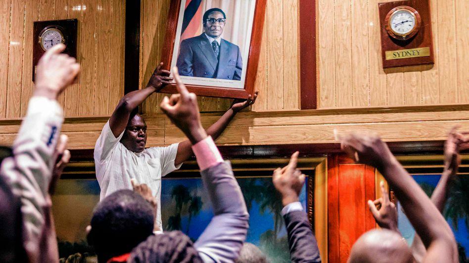Ein Mann nimmt in Harare ein Porträt von Präsident Mugabe von der Wand.