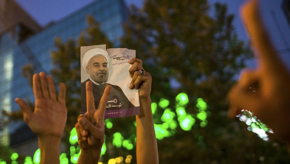 Supporters of moderate cleric Hassan Rohani hold a picture of him as they celebrate his victory in Iran's presidential election in Tehran.