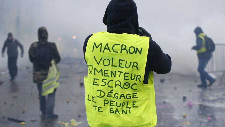 """""""Macron, Dieb, Lügner, Gauner, verschwinde, das Volk verbannt dich"""", steht auf dieser Weste."""