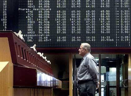 Händler vor der Kurstafel der Dax-Werte: Der Blick auf den Index zwingt Fondsmanager zu prozyklischen Käufen und Verkäufen - Gift für die Kasse der Anleger