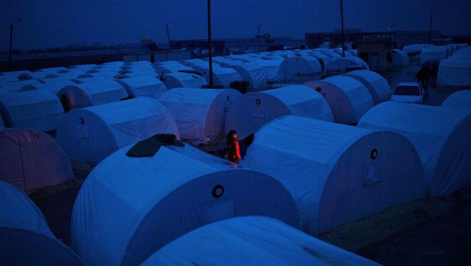 Syrisches Flüchtlingslager: Eine Frau wärmt sich an einem Feuer