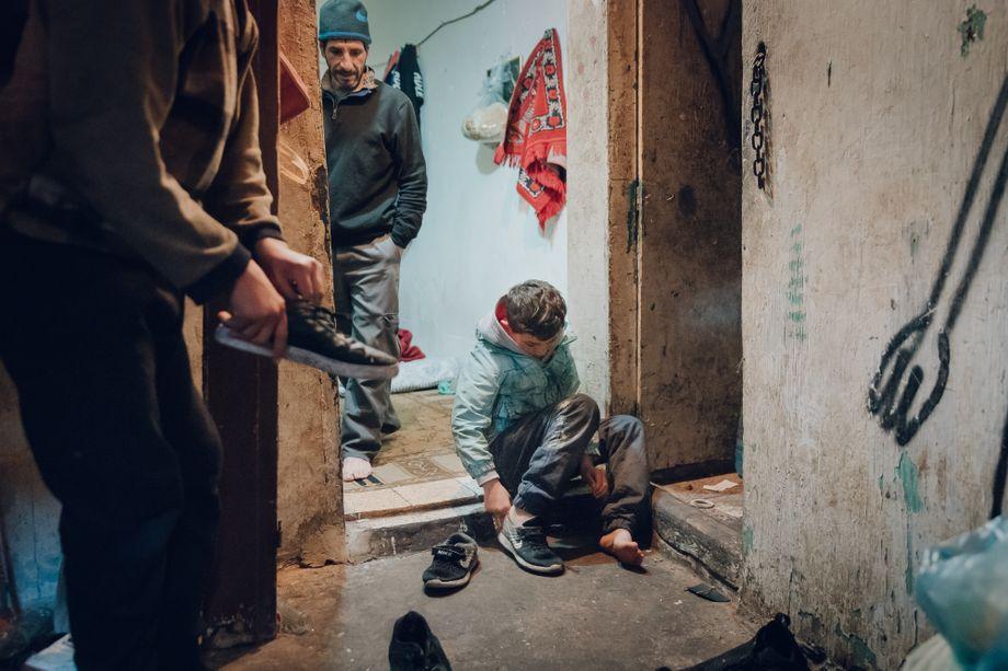 Wael sitzt am frühen Morgen auf der Schwelle seines Schlafzimmers, das er sich mit seinem Vater (M.) und anderen Geflüchteten teilt und zieht seine Schuhe an