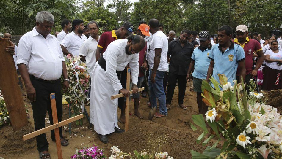 Trauernde an Gräbern von Opfern des Terroranschlags