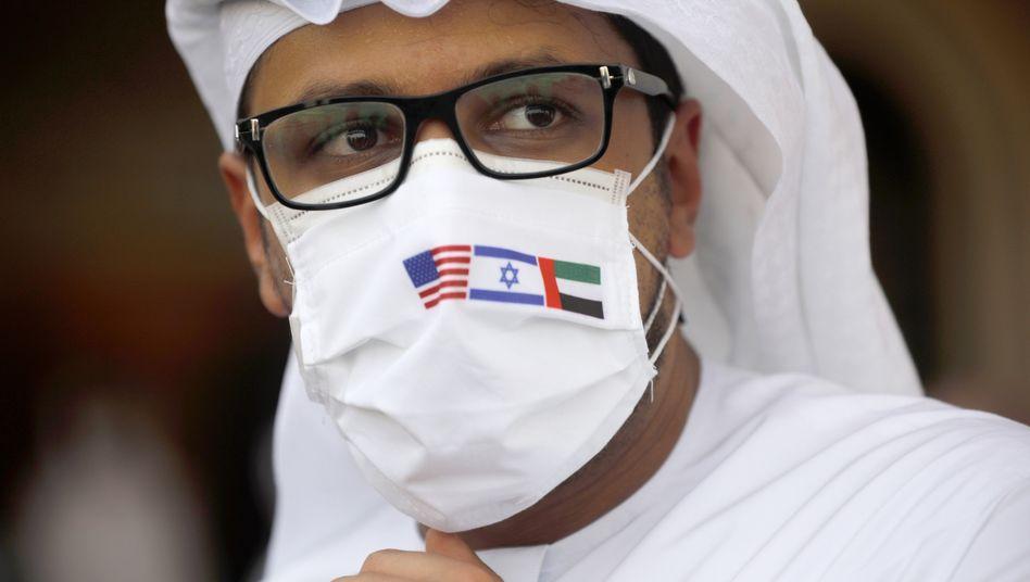 Ein Mann mit Mundschutzmaske, verziert mit den Flaggen der USA, Israels und der Vereinigten Arabischen Emirate