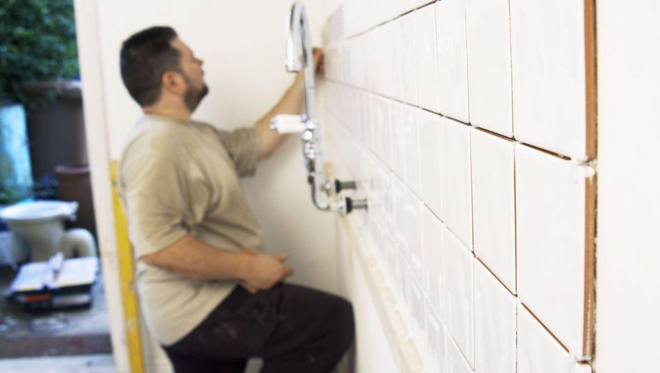 Fliesenleger bei der Arbeit (Archivbild)