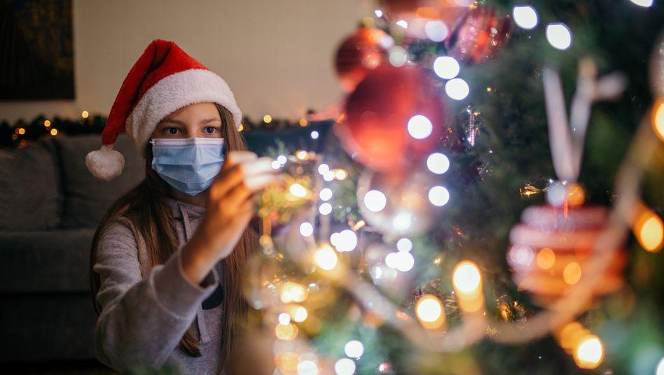 Weihnachten 2020: Mit Mund-Nasen-Schutz vorm Tannenbaum