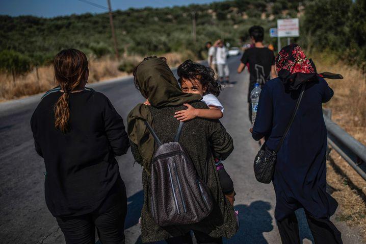 Zwischen den Lagern: Eine Migrantin trägt am 1. September ein Kind auf der Insel Lesbos eine Straße entlang