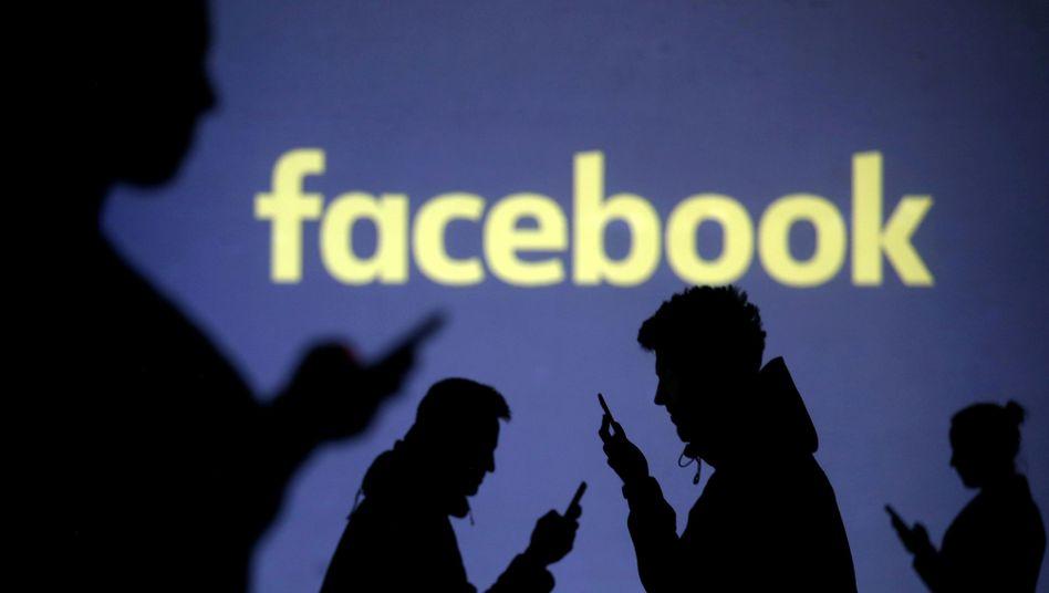 Smartphone-Nutzer vor Facebook-Logo