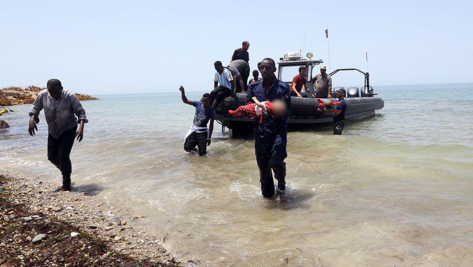 Mitglieder der libyschen Küstenwache tragen die Leichen zweier ertrunkener Kleinkinder aus dem Wasser