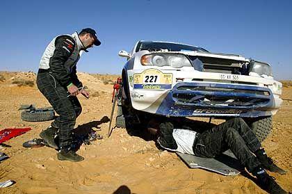 Zwangspause: Luc Alphand und sein Co-Pilot Matthew Stevenson mussten inmitten der tunesischen Wüste ihren BMW X5 reparieren