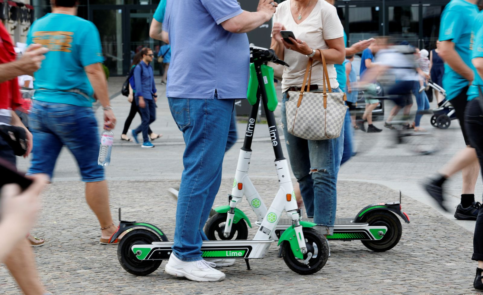 People unlock electric scooters by California-based bicycle rental service Lime with a mobile phone at the Brandenburg Gate in Berlin