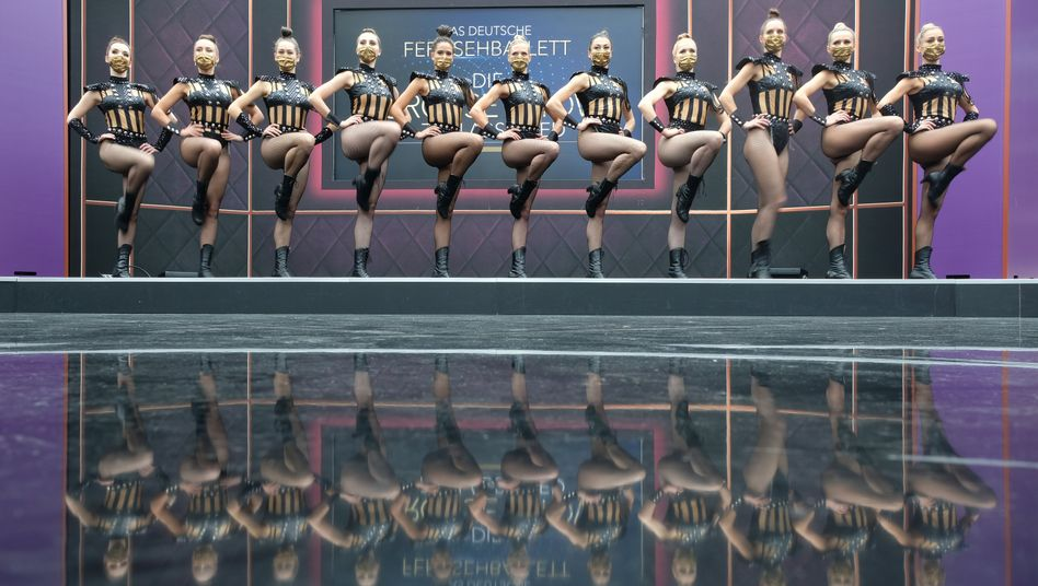 Fernsehballett-Tänzerinnen posieren mit Masken