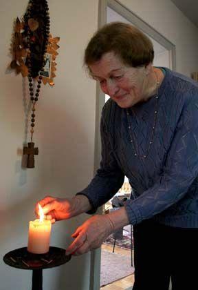 """Anni Fischer zündet in ihrer Wohnung eine Kerze für Benedikt XVI. an: """"Ich hoffe, dass ihm die Kardinäle viel Arbeit abnehmen"""""""