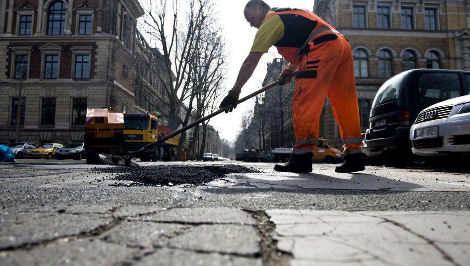 Ein Straßenbauer in Leipzig bei der Arbeit - den Städten droht ein Rekorddefizit