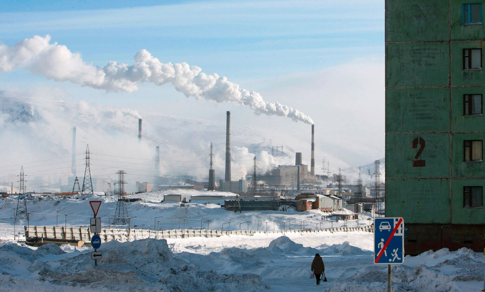 A woman walks near a nickel mine in the arctic city of Norilsk