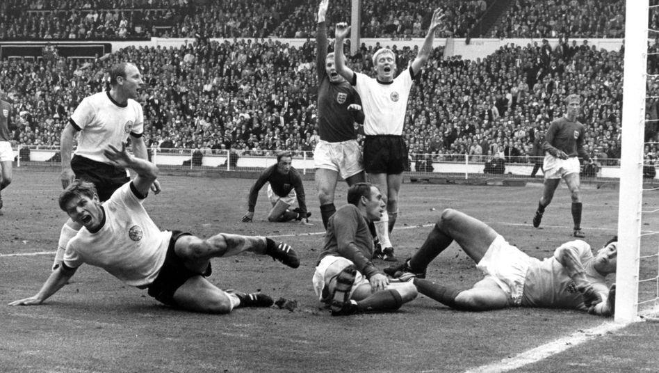Jack Charlton (r.) kann beim Tor des deutschen Nationalspielers Wolfgang Weber (l.) nur zuschauen - am Ende gewann England 1966 in Wembley