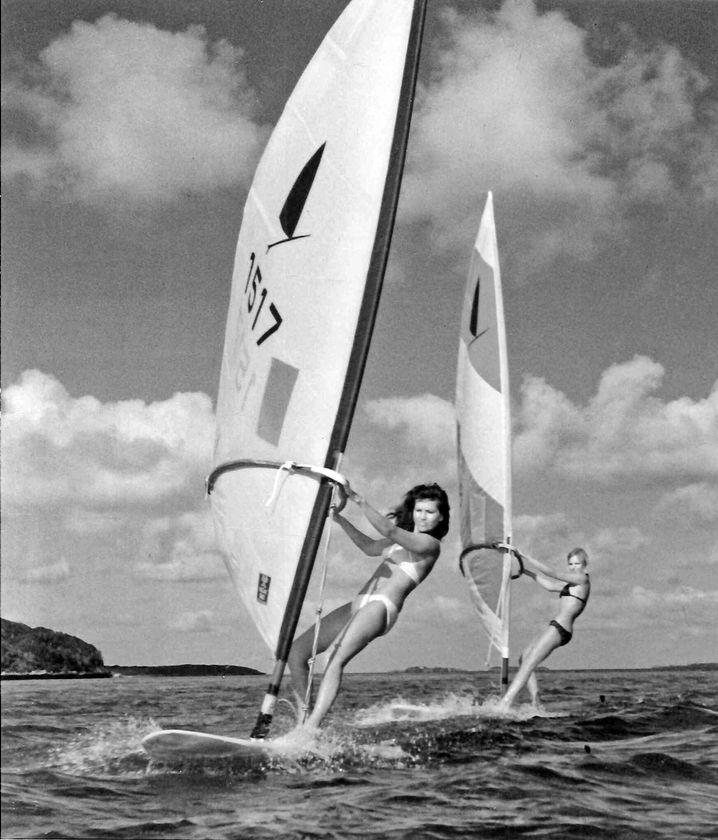 Junge Frauen surfen auf einem See 1974