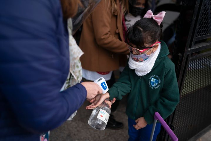 Fiebermessen vor der Schule: Ein Mädchen in Buenos Aires