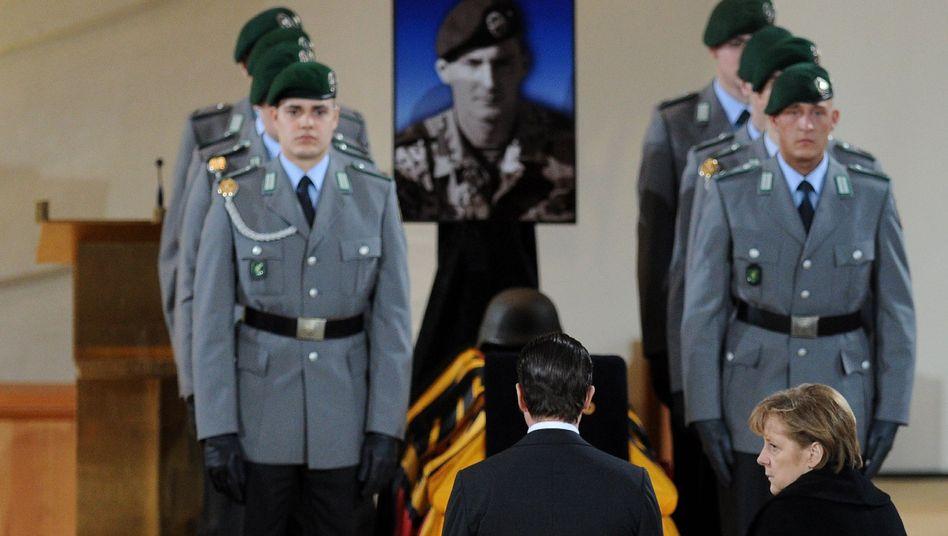 Minister Guttenberg, Kanzlerin Merkel in Regen: Tiefe Trauer um die drei toten Soldaten