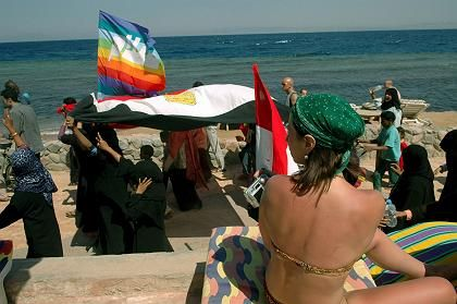 A tourist watches Egyptians demonstrate against terrorism in Dahab on April 25, a day after three bombs killed18 people there.