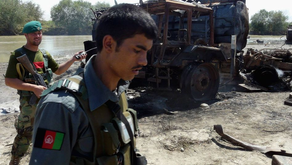Two Afghan policeman inspecting the site of the Sept. 4, German-ordered bombing in Kunduz. The attack killed numerous civilians, possibly dozens.