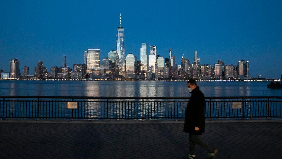 Ein Passant mit Maske vor der Skyline von New York City, das besonders schwer von der Coronavirus-Pandemie betroffen ist