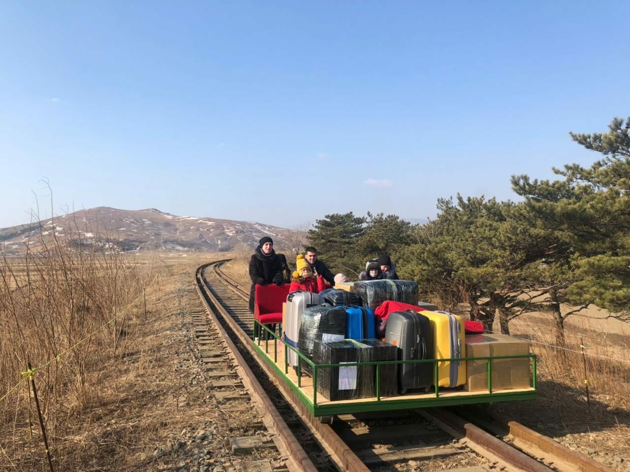 Russian diplomats use a hand-pushed rail trolley while crossing the demarcation line between North Korea and Russia