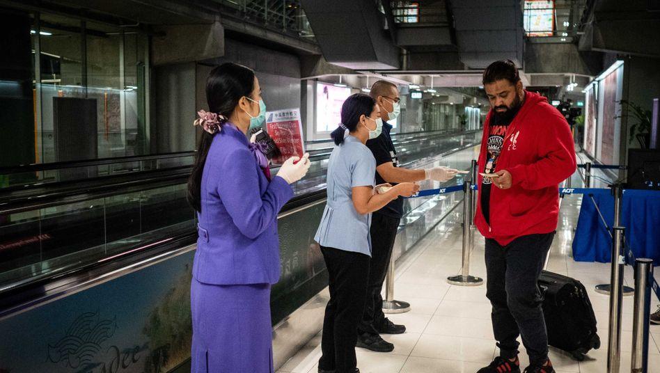 Am Flughafen von Bangkok wird die Temperatur von Reisenden aus Wuhan gecheckt