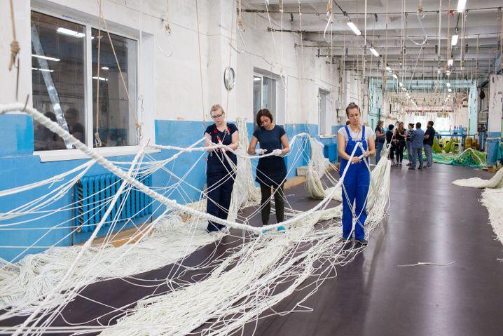 Frauen verknüpfen Seile, die aus Nylonfäden bestehen, die von Maschinen in einer zweiten Halle zu Kordeln geflochten werden