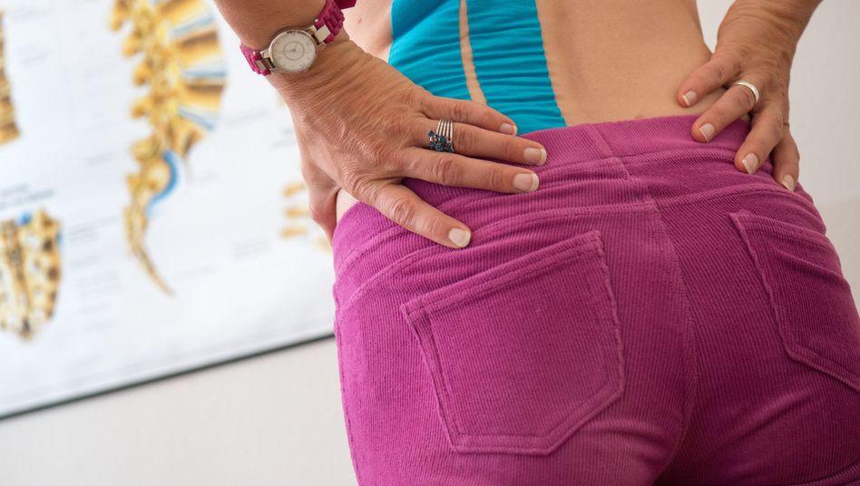 Frau mit Rückenschmerzen in einer Physiotherapiepraxis in Dresden