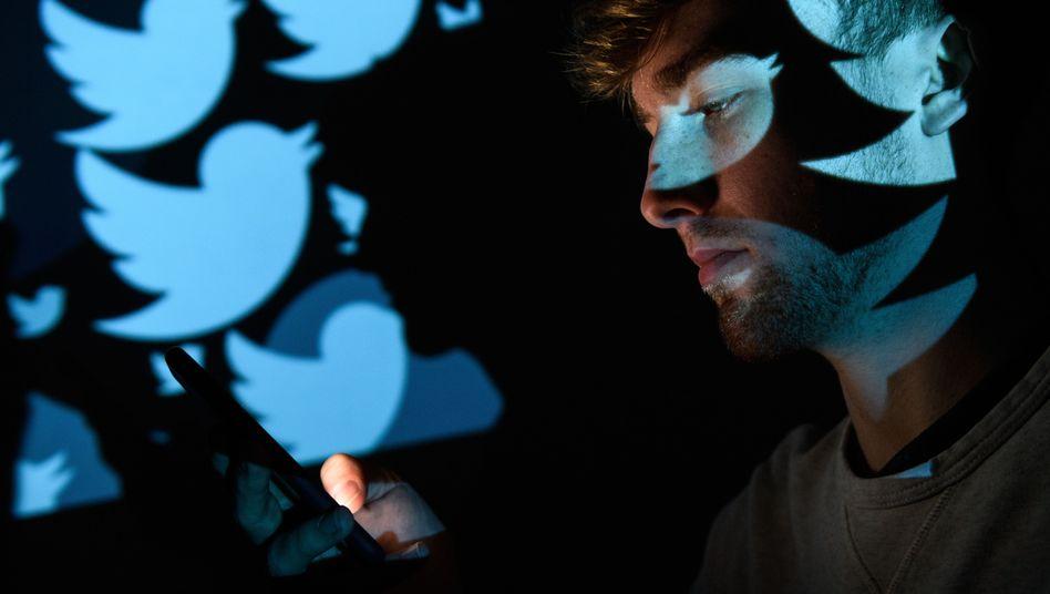 Mann vor Twitter-Logos