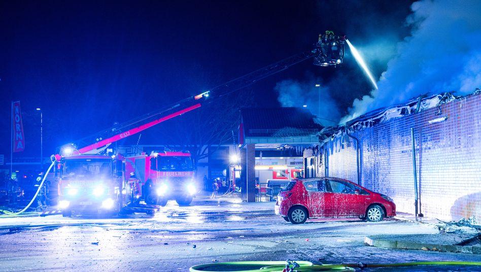 Feuerwehrleute löschen in Berlin einen brennenden Supermarkt: Feuerwerkskörper seien explodiert und umhergeflogen, berichten die Einsatzkräfte