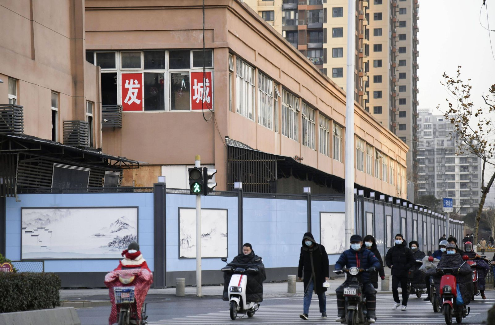 WHO probe into coronavirus origins in Wuhan People wearing face masks walk and ride motorcycles past the Huanan seafood