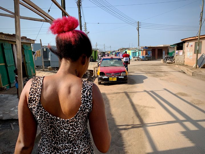Regina Nettey in her neighborhood. For five years, she has regularly been lightening her skin in the hopes of getting a better life.