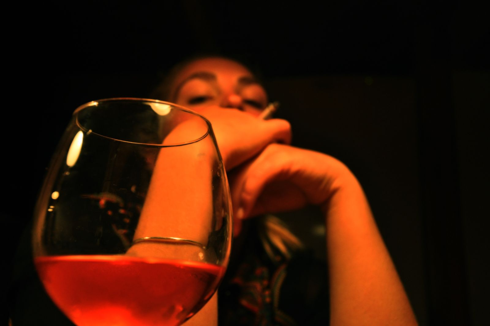 Close-Up Of Wineglass By Woman Smoking Against Black Background