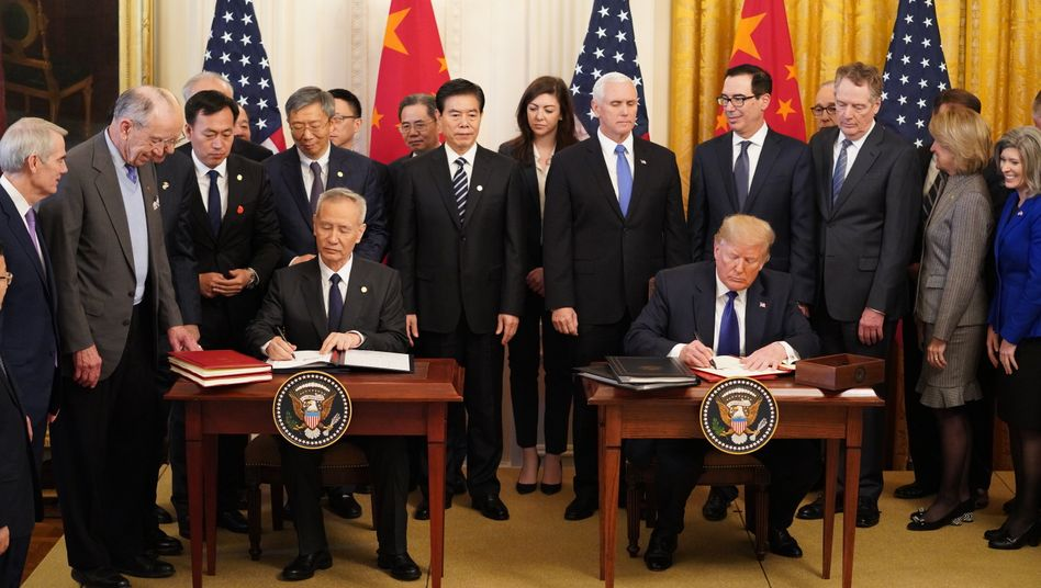 Foto mit Seltenheitswert: US-Präsident Trump (Tisch r.) und Chinas Vizepremier Liu He unterzeichnen ein gemeinsames Handelsabkommen