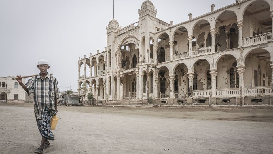A man in Massawa, Eritrea walks in front of the ruined Banca d'Italia building, left as a relic of the war with Ethiopia.